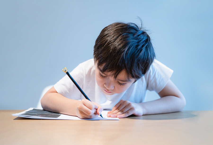Kid writing answers on worksheets